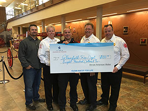 image of firefighters holding a grant check from Illinois American Water