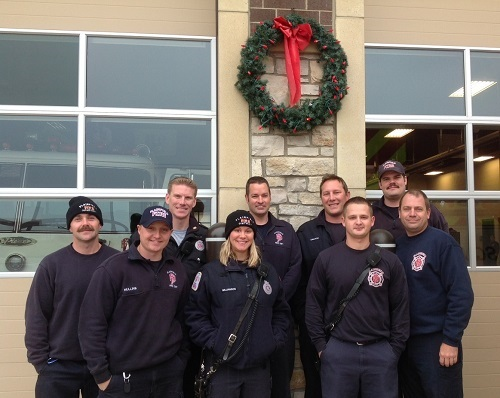 group of firefighters standing in front of a holiday wreath