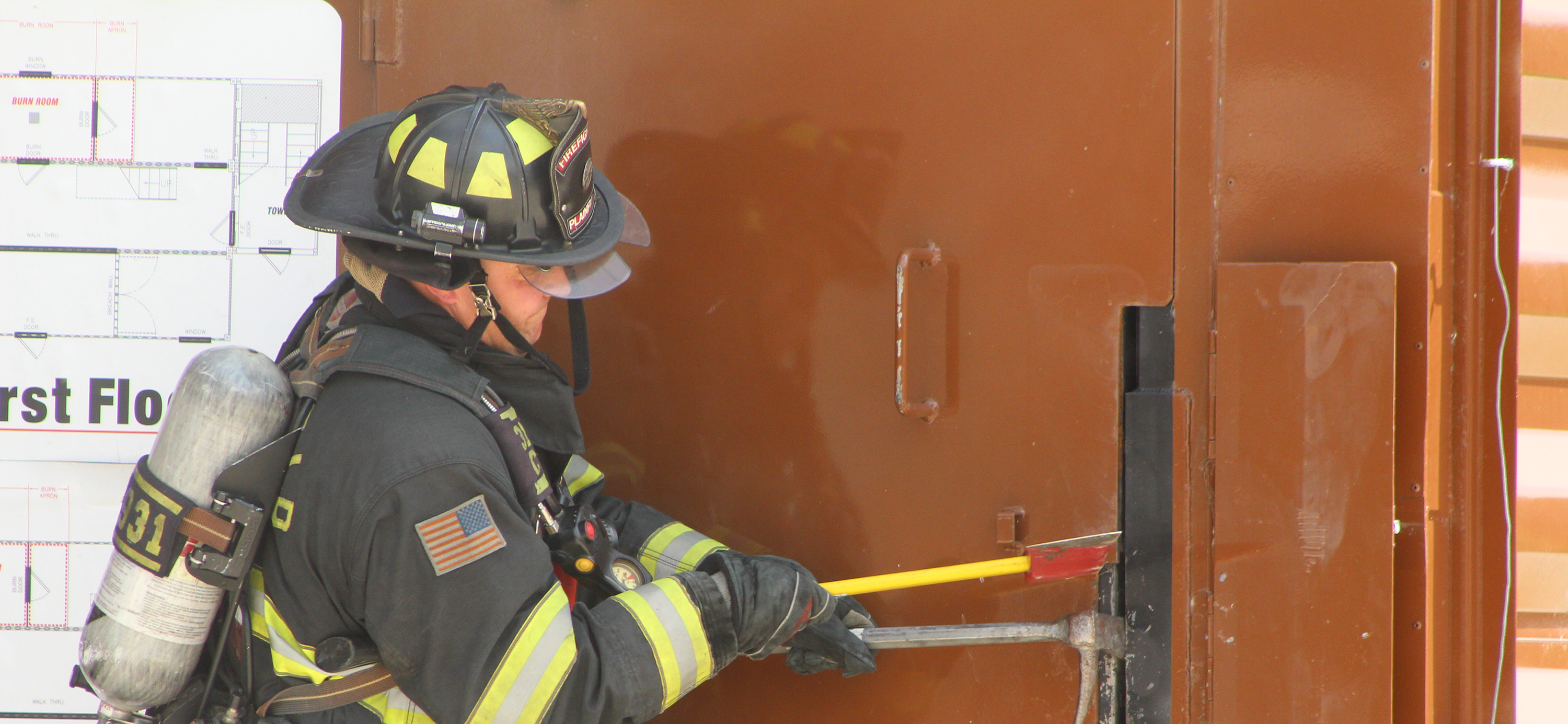 firefighter forcefully opening a door to get inside the building