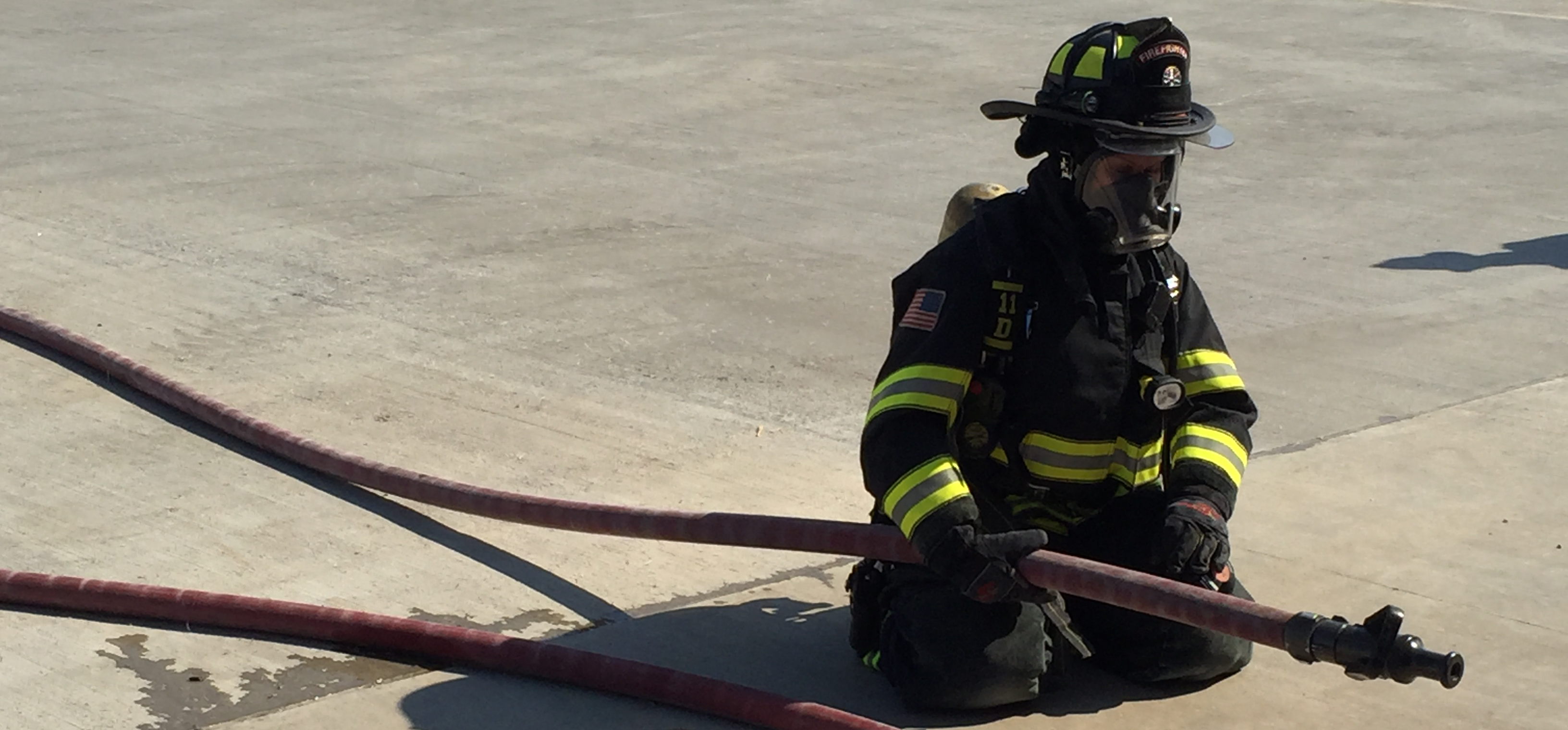 firefighter getting a fire hose ready to go